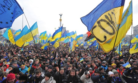 "Ukrainian opposition supporters wave Ukainian and European flags during a mass rally on Independence Square in Kiev on December 15, 2013. At least 200,000 pro-European demonstrators began a mass rally in the Ukrainian capital on December 15 in a fresh show of force against President Viktor Yanukovych after his failure to sign a key EU agreement.  Opposition parties have called on ""all Ukrainians"" to mass on Independence Square, where demonstrators angered by Yanukovych's failure to sign the EU pact have held rolling protests for over three weeks.  AFP PHOTO/ SVIKTOR DRACHEV"